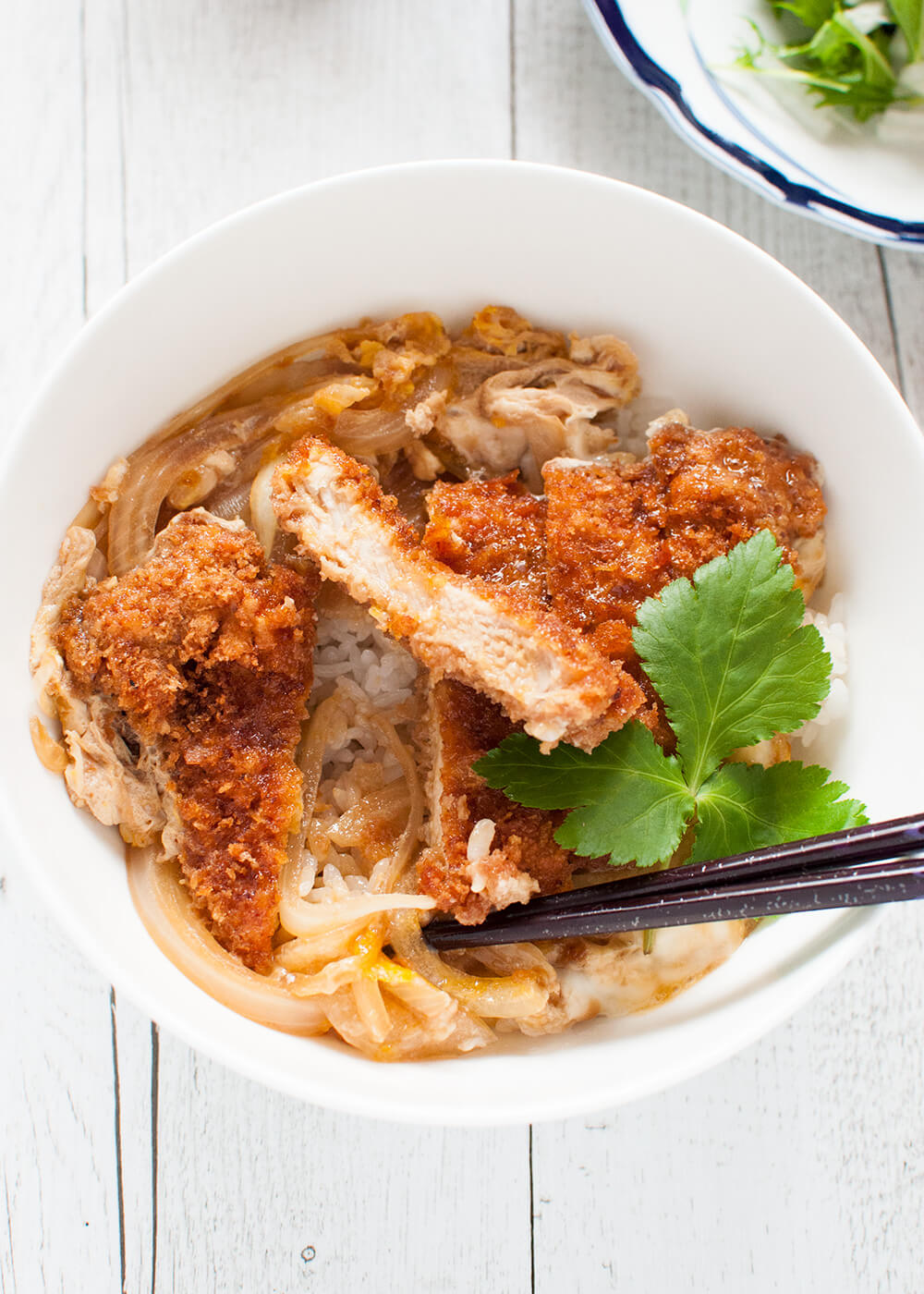 Katsu-don (カツ丼), is a very filling main dish. A bowl of rice topped with tonkatsu (deep fried crumbed pork cutlet), onion and beaten egg, cooked in dashi with sweet soy sauce.