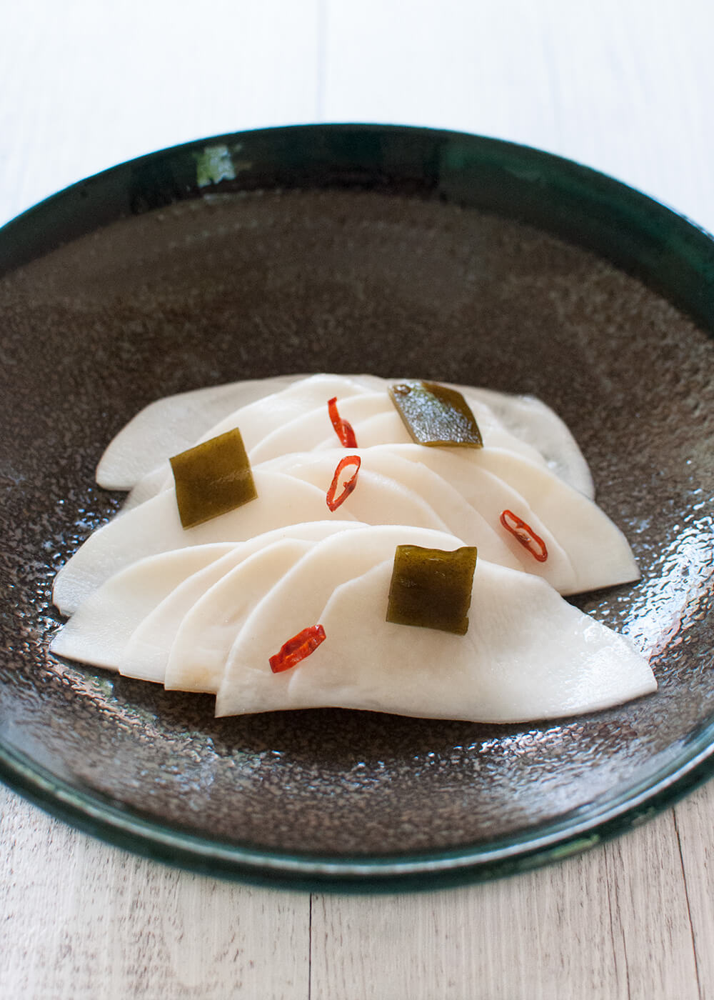Thinly sliced turnip is marinated in sweet vinegar with konbu and chilli. Crunchy turnip with sweet and sour flavour – it's greatwith rice and goes well with drinks as nibbles.