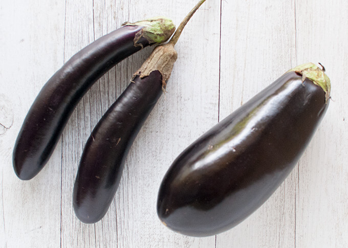 Thin long (small) eggplants and a large eggplant.