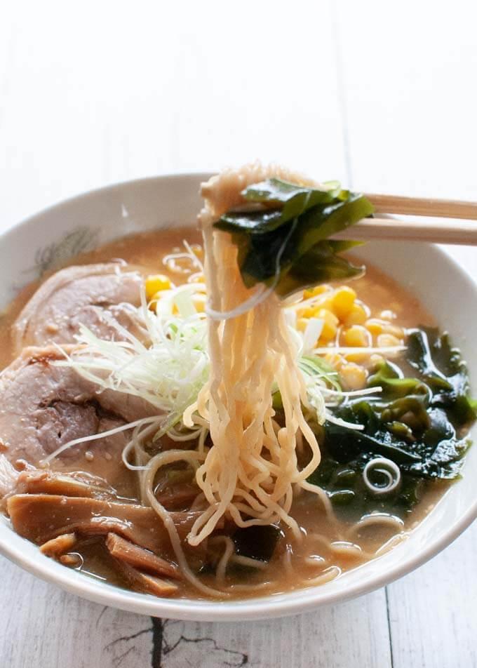 Lifting strands of ramen noodles from Sapporo Miso Ramen