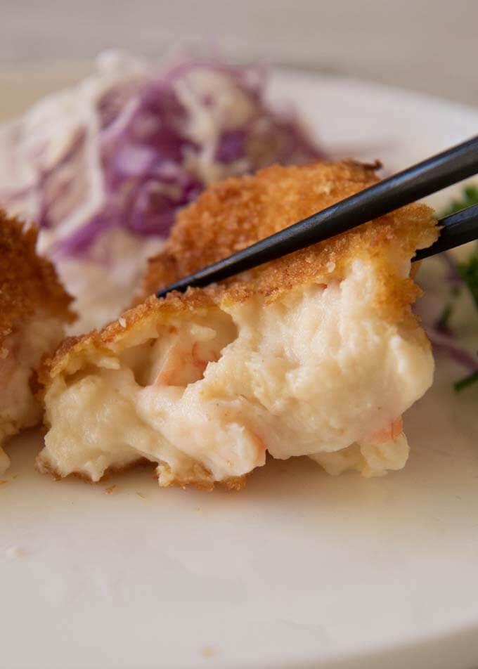Half Creamy Shrimp Croquettes squeezed with chopsticks showing creamy béchamel inside.