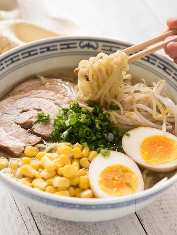 Hero shot of Shio Ramen with noodles lifted up with chopsticks.