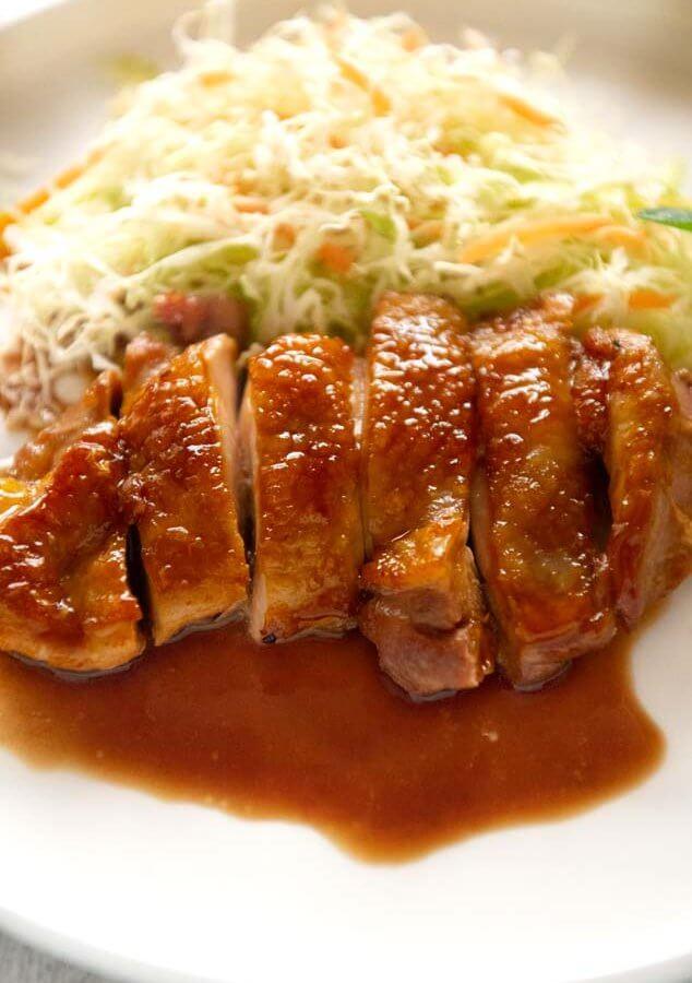 Hero shot of Teriyaki chicken on a white plate with shredded vegetables.
