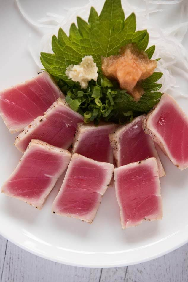Serving Tuna Tataki with condiments - grated ginger, chopped shallots and momiji oroshi (grated daikon with chilli) on a perilla leaf - before pouring Ponzu Dressing.