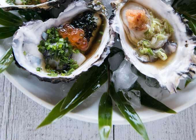 Zoomed-in photo of Oyster with Tosazu Dressing on crashed ice and bamboo leaves.
