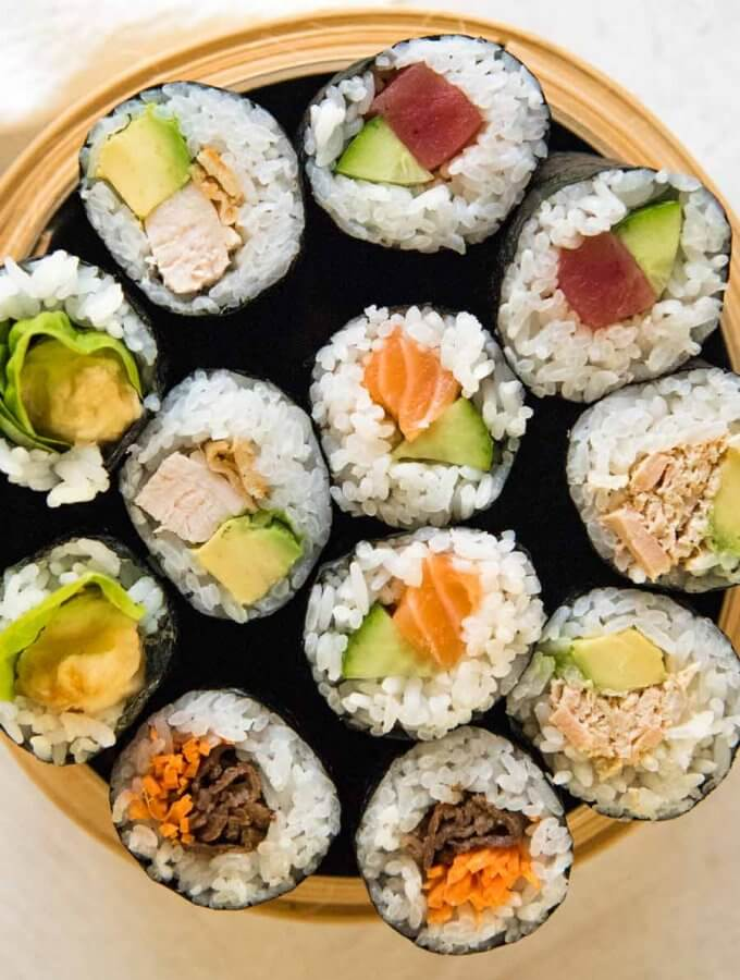 Top-down photo of 12 sushi rolls with 6 different fillings fit in a bamboo container.