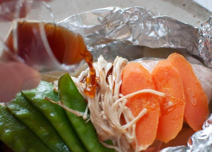 Pouring Ponzu Dressing over cooked salmon and vegetables.