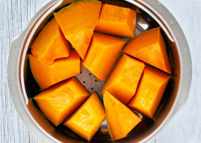 Pumpkin pieces in a steaming pot.