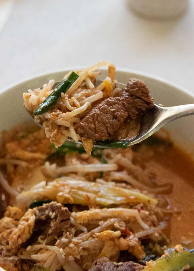 Zoomed-in photo of Korean Beef Soup with Rice, scooping with a spoon.