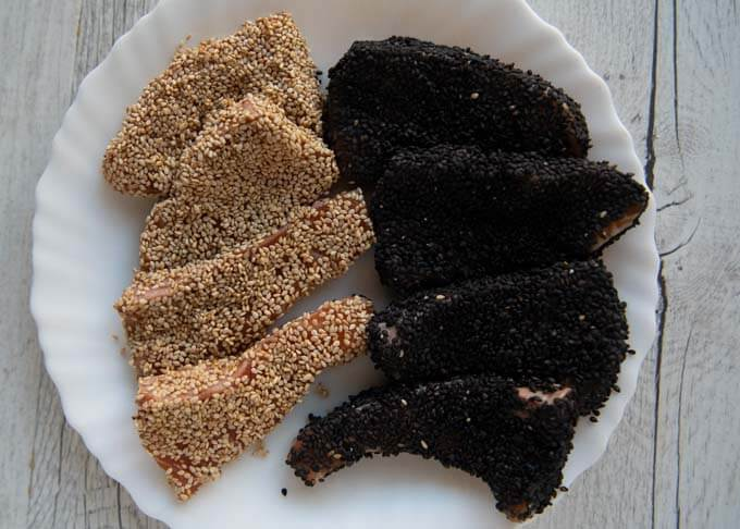 Some salmon pieces coated in white sesame seeds, some in black sesame seeds.