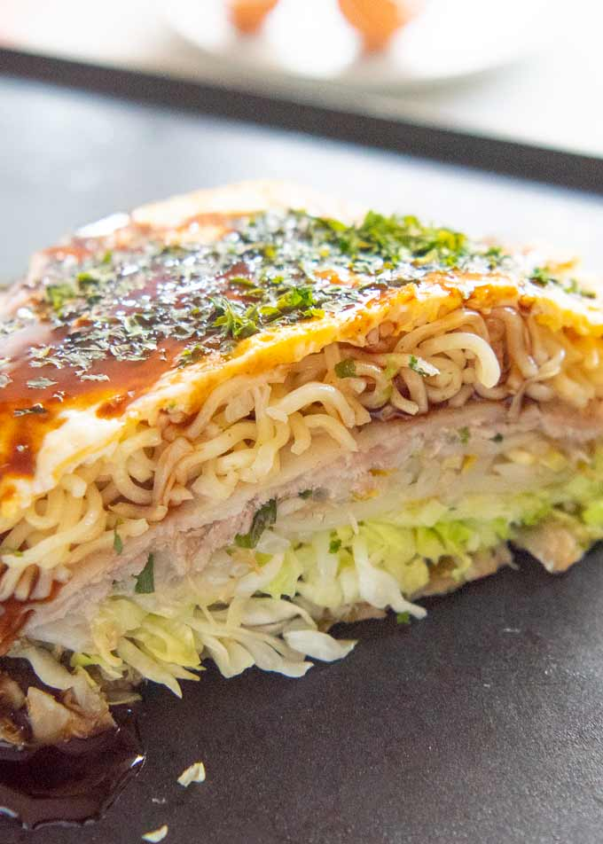 Zoomed-in photo of okonomiyaki cut in half, showing the layers of ingredients.