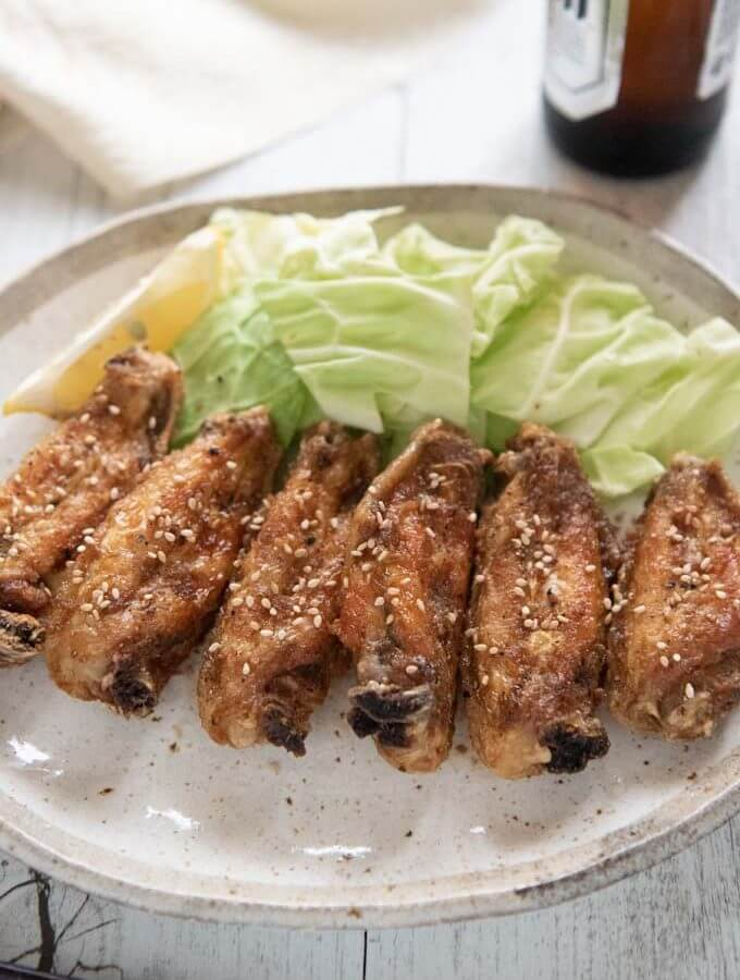 Hero shot of Furaibou-style fried chciken wings on a plate served with cabbage pieces.