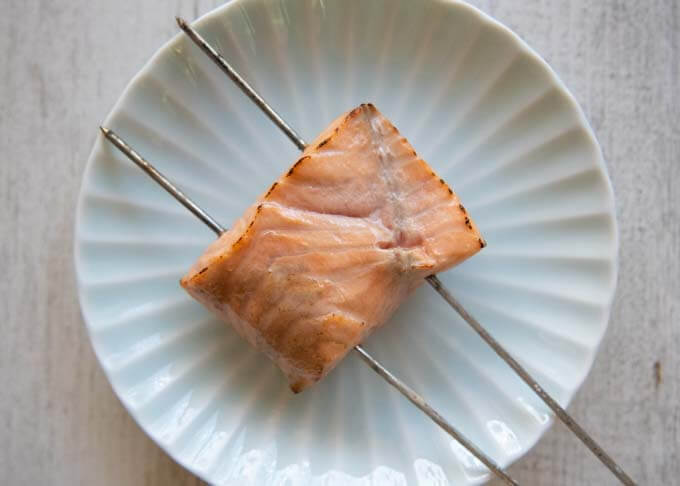 Searing a salmon fillet over the cook top.