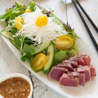 Hero shot of Tuna Sashimi Salad with Garlic Sesame Dressing on the side.