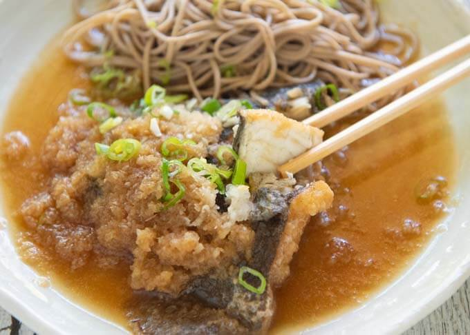 Zoomed-in photo of Flounder Mizore-ni (Simmered Flounder in Grated Daikon), picking up a fish piece with chopsticks.