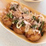 Hero shot of Takoyaki in a traditional serving tray.