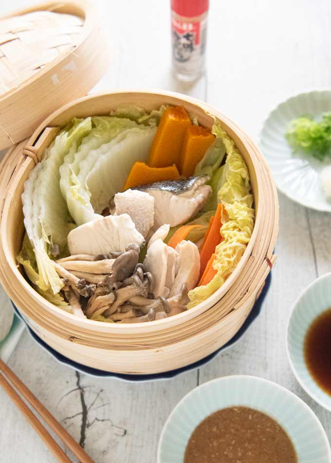Hero shot of Steamed Chicken and Fish with Vegetables served with two dipping sauces.