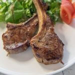 Hero shot of Pan-Fried Lamb Chops with Miso Marinade served with salad and tomato wedges.